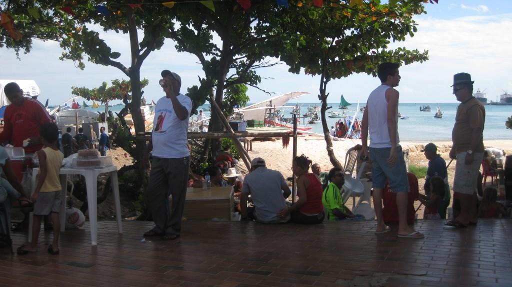 Die Leute beobachten die Parade der typischen Jangadas (mit den dreieckigen Segeln)