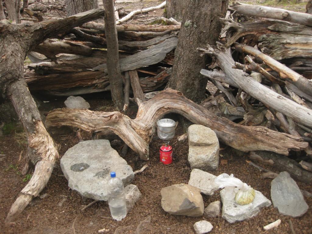 Auf dem Campingkocher in einer geschützten Ecke kochen im Nationalpark Torres del Paine, Chile