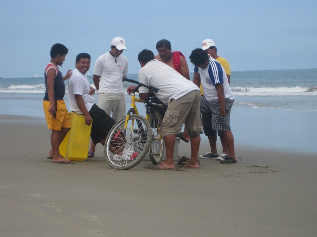 """Fischlieferung mit dem Fahrrad (den Strand entlang """"angereist""""). Nach Verhandlung und Schwätzchen: Zwei Fische behält sich der Lieferant - eingespannt in den Gepäckträger."""