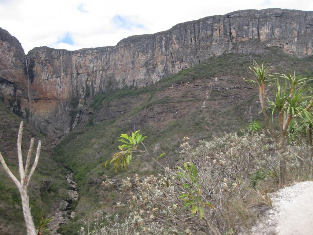 Im Hintergrund der Wasserfall, am Bildrand rechts Teile des steinigen Wegs bergab. Unten im Tal sieht man den Flusslauf.