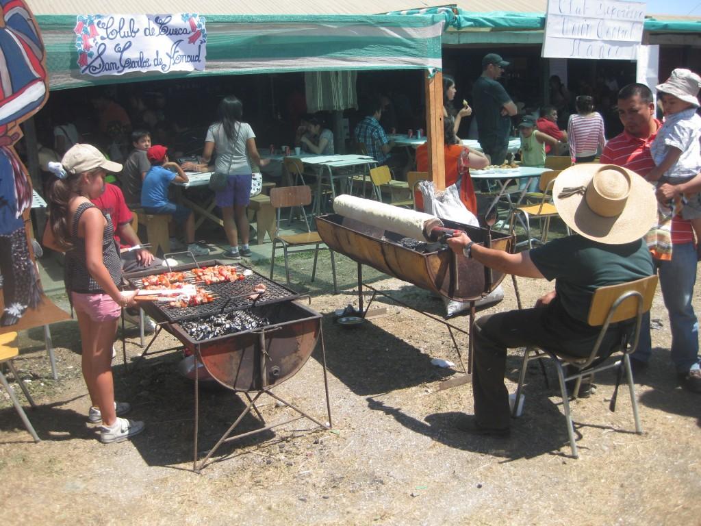 Rechts Chochoca al palo, links Fleischspieße auf dem Grill. Muestra Costumbrista Ancud