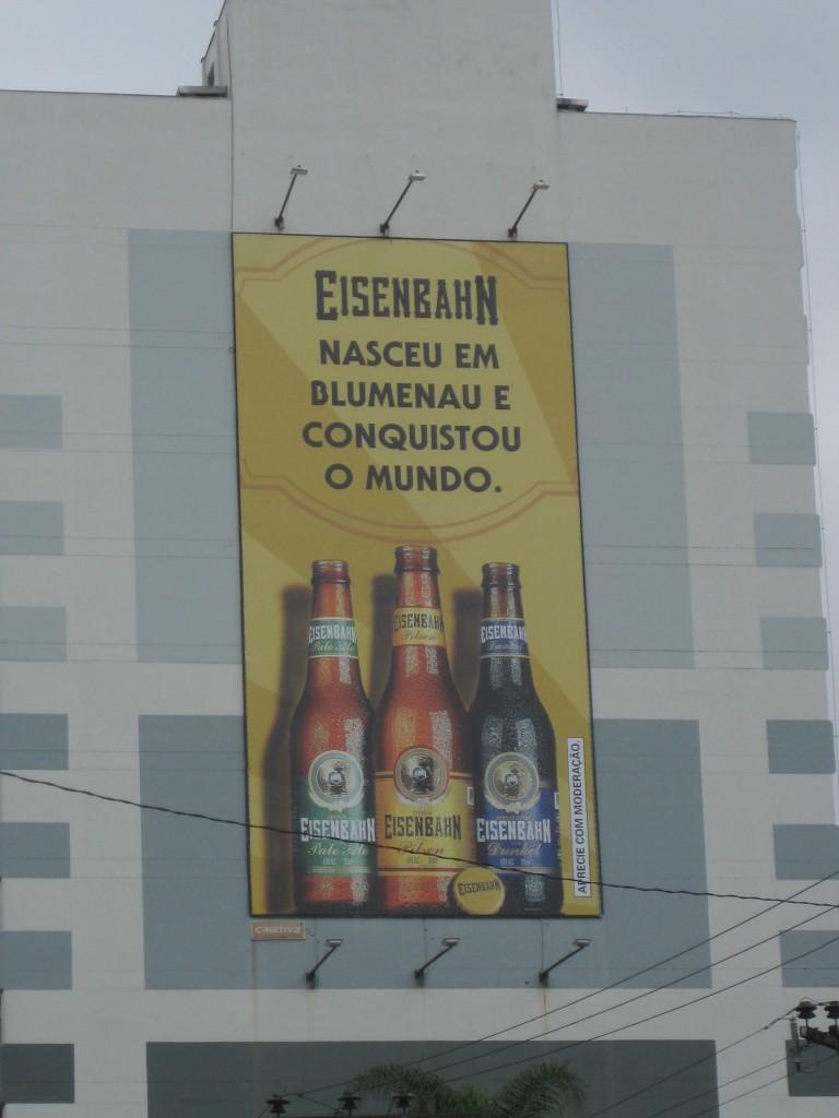 """Werbung für das brasilianische Bier der Brauerei """"Eisenbahn"""", Werbetext: """"In Blumenau geboren, die Welt erobert."""""""